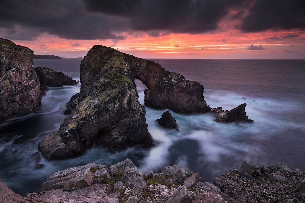 Natural rock archway at sunset, West Lewis, Scotland.