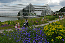New tropical greenhouse at RHS Wisley, Families walking around garden; blue geraniums in foreground, Surrey UK