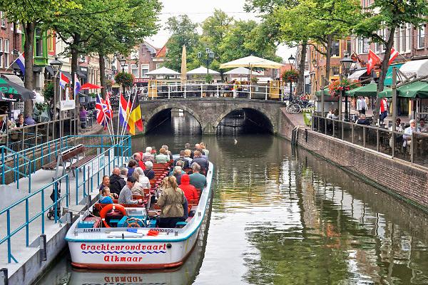Nederland, the Netherlands, Alkmaar, 28-8-2018Toeristen wachten in een open rondvaartboot op het vertrek voor een tochtje door de grachten van deze stad in Noord Holland . Toerisme is een grote inkomstenbron voor de bv Nederland.Foto:Flip Franssen