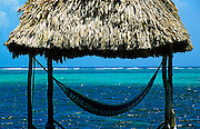 Cabana with hammock overlooking aqua tropical waters, Ambergris Caye, Belize.