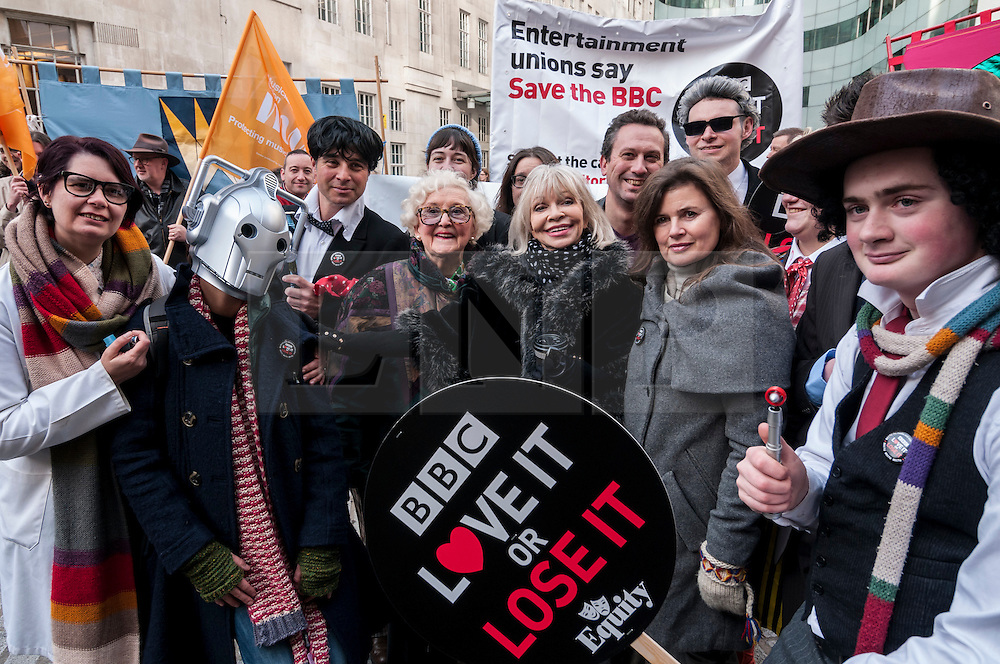 """© Licensed to London News Pictures. 23/11/2015. LONDON, UK. June Hudson (inventor of Doctor Who's iconic long scarf) stands with former Doctor Who girls, Katy Manning and Sophie Aldred as fans of Doctor Who known as """"Whovians"""" and other supporters of the BBC gathered outside Broadcasting House in central London to oppose the threat of 20% government cuts to the Corporation. Photo credit : Stephen Chung/LNP"""