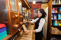 Side view portrait of female salesperson dispensing coffee beans into paper bag at store