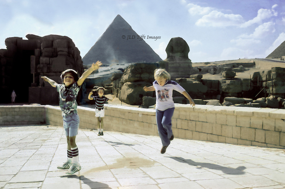Two boys and a girl aged 8 to 11 jumping in the son et lumiere theater platform. Each is caught in the air.  Sphinx and pyramid of Chephren (Khafre) beyond, with other temple ruins on each side.