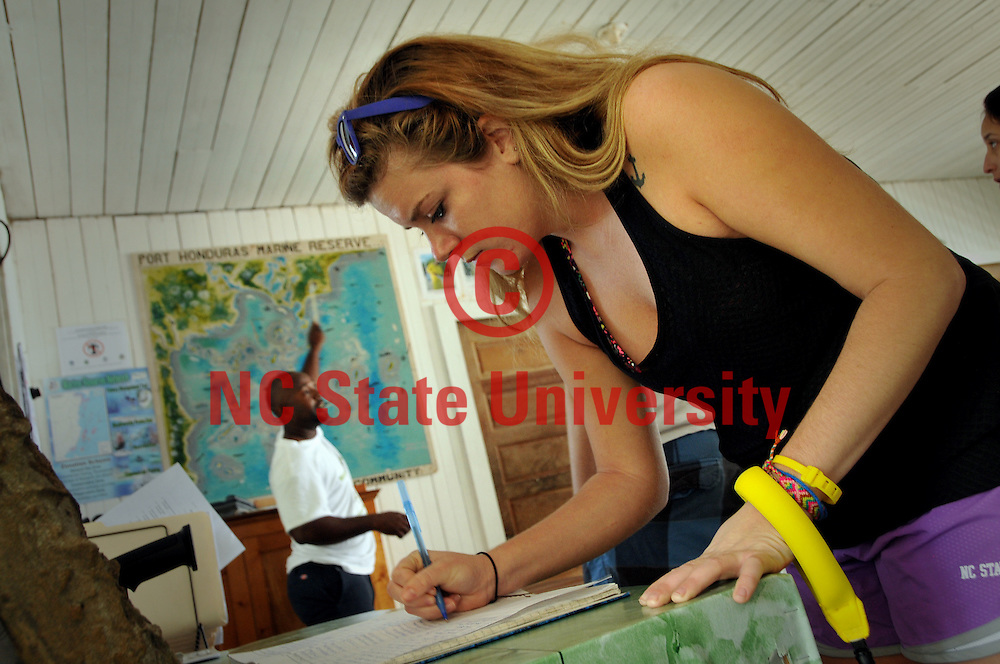 Chelsea Bowman signs the guest registry during a visit to the Port Honuras Marine Reserve.