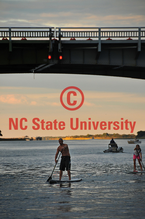 A paddle boarder heads along the Intracoastal Waterway at the Wrightsville Beach bridge.