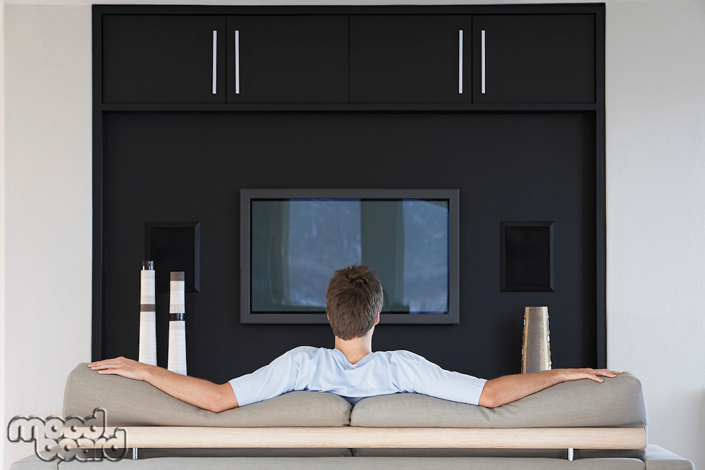 Man sitting in front of flat screen television at home back view