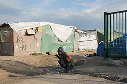 """Calais, Pas-de-Calais, France - 16.10.2016    <br />     <br />  A refugee brush his teeth  in front of a booth with the slogan British Hotel in the """"Jungle"""" refugee camp on the outskirts of the French city of Calais. Many thousands of migrants and refugees are waiting in some cases for years in the port city in the hope of being able to cross the English Channel to Britain. French authorities announced that they will shortly evict the camp where currently up to up to 10,000 people live.<br /> <br /> Ein Fluechtling putzt sich die Zaehne vor einer Huette mit der Aufschrift """"British Hotel"""" im """"Jungle"""" Fluechtlingscamp am Rande der franzoesischen Stadt Calais. Viele tausend Migranten und Fluechtlinge harren teilweise seit Jahren in der Hafenstadt aus in der Hoffnung den Aermelkanal nach Großbritannien ueberqueren zu koennen. Die franzoesischen Behoerden kuendigten an, dass sie das Camp, indem derzeit bis zu bis zu 10.000 Menschen leben Kürze raeumen werden. <br /> <br /> Photo: Bjoern Kietzmann"""