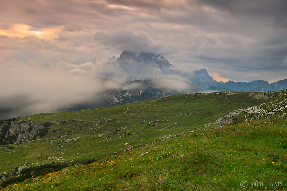 Stormy clouds at sunset above the plains of the Tre Cime di Lavaredo in Veneto, with the Croda Rossa d'Ampezzo in the background. Dolomites, Italy