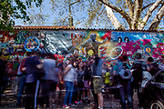 Visitors at the Prague Lennon Wall looking at a grafitti of former president Vaclav Havel andother grafitti. Once a normal wall, since the 1980s it has been filled with John Lennon-inspired graffiti and pieces of lyrics from Beatles' songs.