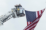 Middletown, New York - Mechanicstown firefighters in a tower salute as marchers in the Middletown-Town of Wallkill Memorial Day parade head down Highland Avenue on May 25, 2015.
