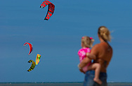 A mother and daughter watch as kite surfers fly through the air over the waters of the North Sea. (Photo © Jock Fistick)