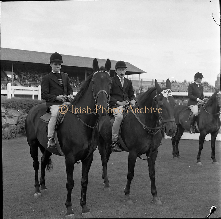 """07/08/1962 <br /> 08/07/1962 <br /> 07 August 1962 <br /> Dublin Horse show at the RDS, Ballsbridge, Dublin, Tuesday. Among six sharing 1st place in Jumping Competition """"A"""" (children) over a special course were, Brian Henry, Coleraine (left) on """"Tristan"""" and Geogre Stewart of Lisburn on """"Shady Nook""""."""