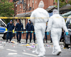 © Licensed to London News Pictures . 12/08/2018. Manchester , UK . Police conduct a fingertip search at the scene . Police have closed off Claremont Road in Moss Side after a shooting overnight during the annual Caribbean Carnival celebrations . Ten people are in hospital . Photo credit : Joel Goodman/LNP