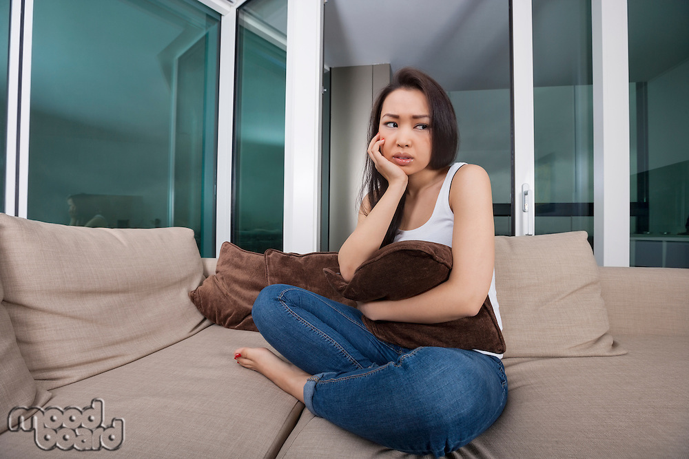 Full length of tensed young woman holding cushion on sofa in living room