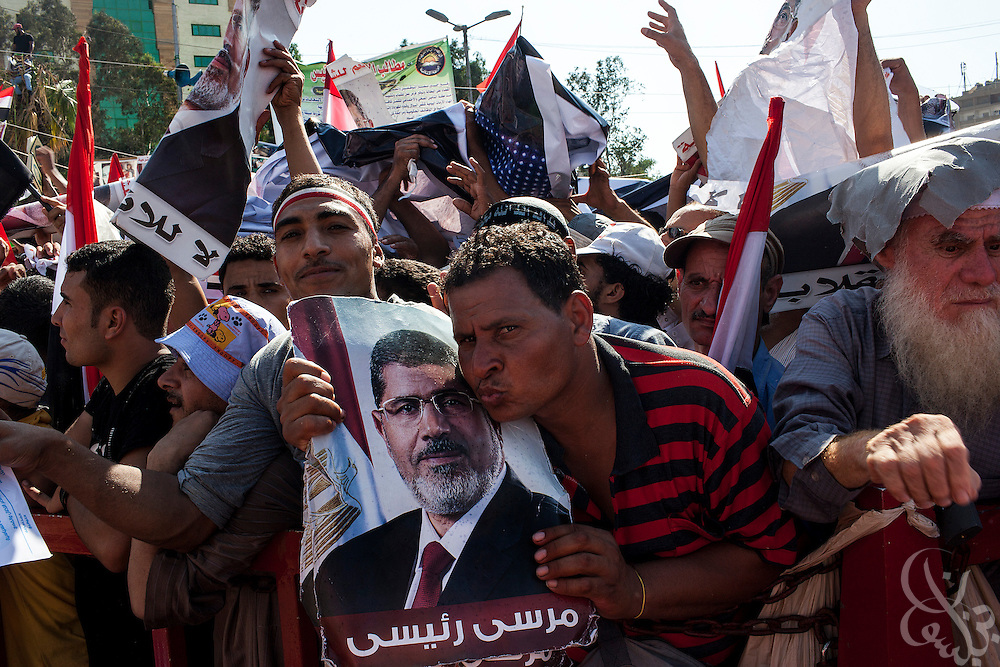 A supporter of deposed Egyptian president Mohamed Morsi kisses a poster of the ex-leader as thousands take part in the continuing large scale demonstrations and sit-in around the Rabaah al-Adawia mosque and square in the Nasr City district of Cairo Friday July 26, 2013.  The supporters are demanding the reinstatement of the deposed President and are opposed to the Egyptian military, which they say has undertaken an undemocratic coup.