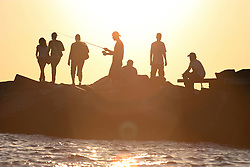 People sitting on breakwater at sunset