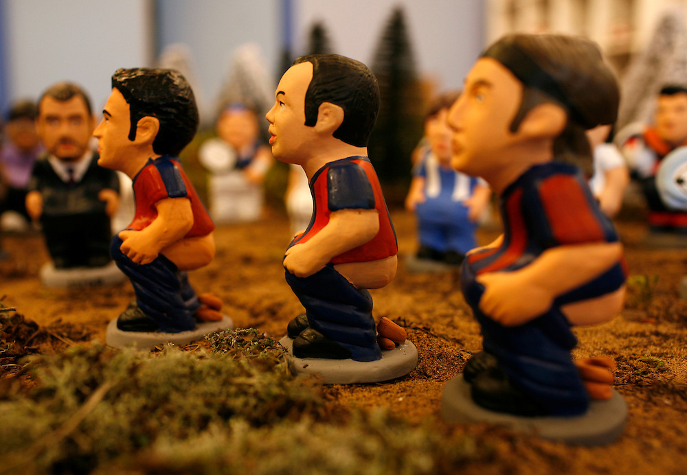 "Torroella de Mongri, Spain, 19 November 2009. .A company in Torroella de Montgrí (Girona, Spain) called ""caganer.com"" specialized in the production of ""caganers"" unveiled today  the new figures for Christmas as F.C. Barcelona players, Xavi, Iniesta and Zlatan Ibrahimovic..A ""Caganer"" is a small figure from Catalonia, usually made of fired clay,  and depicted as squating person in the act defecating. .""Caganer"" is Catalan for pooper. It fomrs part of one of the typical figures of  the manger or ""Nativity"" scene together with Mary, .Joseph and the baby Jesus but hidden in a corner. It is a humorous figure, originally portraying a peasant wearing a .barretina (a red stocking hat), and seems to date from the 18th century when it  was believed that the figure's depositions  .would fertilize the earth to bring a properous year. With  the course of the time, the original  personage of this pooping figure .was  substituted with personalities from the political and sports world and other famous personalities."