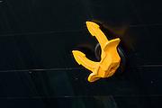 Yellow anchor on hull of ship, close-up