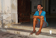 A down-and-out man sits on the front steps of Leon Cathedral in Nicaragua, barefoot and with a styrofoam cup for change.