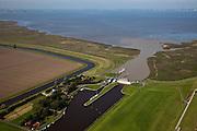 Nederland, Groningen, Oldambt, 08-09-2009; Sluizencomplex bij Nieuwe Statenzijl, op de grens met Duitsland. De spuisluizen zijn uitwaterende sluizen voor de Groninger Boezem, Waterschap Hunze en Aa's. Links de schutsluis tussen Westerwoldsche Aa en de Buiten Aa (geul door de Dollard). Op de kwelder rechts, buitendijks, de vogelkijkhut Kiekkaaste, windmolens in Emden aan de horizon. .Complex of locks in New Statenzijl, on the border with Germany, sluices and lock. Salt marsh and Waddensea..luchtfoto (toeslag); aerial photo (additional fee required); .foto Siebe Swart / photo Siebe Swart
