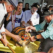 Regional councillor Karl Kiefer holds the spigot and Miss Oktoberfest Vanessa Buttinger and Cambridge Mayor   Doug Craig watch while beer flies everywhere during the Cambridge tapping of the keg, part of the city's Oktoberfest celebrations on Wednesday. <br /> <br /> <br /> IAN STEWART / SPECIAL TO THE RECORD
