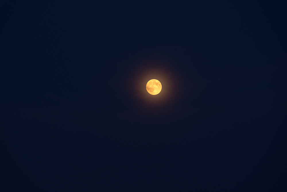 Full moon in a sky filled with smoke from a forest fire.