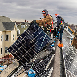 Revision Energy employees installing solar panels on a multi-family home in Lowell, Massachuetts.