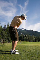 A male golfer pitches on the Whistler Golf Course, Whistler, BC Canada with Whistler Mountain in the background.