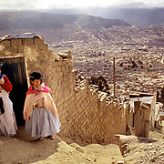 Indigenous Aymaran women chat on the street in El Alto with a spectacular view of the city of La Paz in the valley in the background.