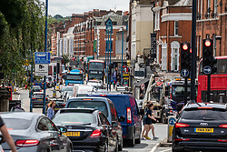 "© Licensed to London News Pictures. 03/07/2020. London, UK. Heavy traffic in Putney Hight Street in South West London as cafes, restaurants, pubs and hairdressers, prepare for the big opening ""Super Saturday"" after Prime Minister Boris Johnson gave the go ahead in his statement to the Nation last week. Photo credit: Alex Lentati/LNP"