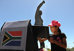 A young girl writes a condolence message as visitors place flowers at the statue of Nelson Mandela at the entrance of the Groot Drakenstein Prison formerly known as the Victor Verster Prison in Paarl, just outside of Cape Town. The statue is at the place Nelson Mandela walked out of prison, a free man, on 11 February 1990, PAARL, SOUTH AFRICA, Sunday, 8th December 2013. Picture by Roger Sedres / i-Images