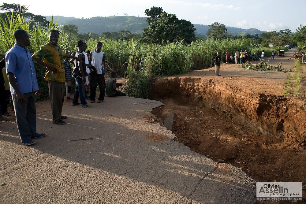 People look at a section of the road that collapsed due to heavy rains near Kpalime, Togo on Thursday October 2, 2008.