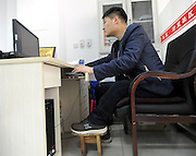 SHENYANG, CHINA - MARCH 28: (CHINA OUT)<br /> <br /> Man Has One Leg Shorter 23 CM Than The Other<br /> <br /> 27-year-old Zhao Qiang sits in front of a computer on March 28, 2014 in Shenyang, Liaoning Province of China Zhao had multiple chondroma when he was 2-year-old which made his left leg grow slower than the right one,  Zhao got an idea to wear a wooden bench on his left leg to keep balance. Hear has been wearing the wooden bench for 14 years. <br /> ©Exclusivepix