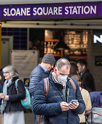 © Licensed to London News Pictures. 11/03/2020. London, UK. A man in a mask looks at his phone outside Sloane Sq Tube Station on the King's Road in Chelsea as Health Minister Nadine Dorries goes in to self-isolation after catching Covid19. Yesterday British Airways cancelled all flights to and from Italy as fears over the Coronavirus disease continues. Photo credit: Alex Lentati/LNP
