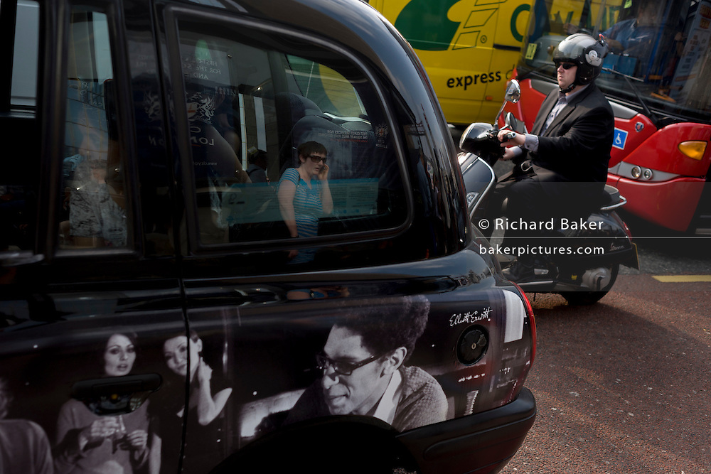 A taxi passenger, commuter traffic and the reflections of a passer-by at a central London bus stop.