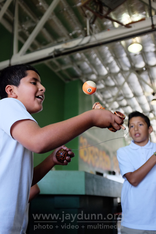 Alejandro Aguilar practices Kendama with a pool ball at the  Breadbox in east Salinas. The wooden ball he's holding in his left hand is light, which makes it harder to catch in a cup.