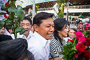 27 FEBRUARY 2013 - BANGKOK, THAILAND:  Pol Gen PONGSAPAT PONGCHAREON (left) and YINGLUCK SHINAWATRA, Prime Minister of Thailand, push through a crowd while they campaign for Pongsapat's election to Governor of Bangkok. Police General Pongsapat Pongcharoen (retired), a former deputy national police chief who also served as secretary-general of the Narcotics Control Board is the Pheu Thai Party candidate in the upcoming Bangkok governor's election. (He resigned from the police force to run for Governor.) Former Prime Minister Thaksin Shinawatra reportedly personally recruited Pongsapat. Most of Thailand's reputable polls have reported that Pongsapat is leading in the race and likely to defeat Sukhumbhand Paribatra, the Thai Democrats' candidate and incumbent. The loss of Bangkok would be a serious blow to the Democrats, whose base is the Bangkok area.    PHOTO BY JACK KURTZ
