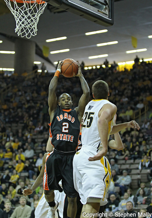 December 04 2010: Idaho State Bengals guard Broderick Gilchrest (2) brings down a rebound as Iowa Hawkeyes guard Eric May (25) looks on during the first half of their NCAA basketball game at Carver-Hawkeye Arena in Iowa City, Iowa on December 4, 2010. Iowa won 70-53.