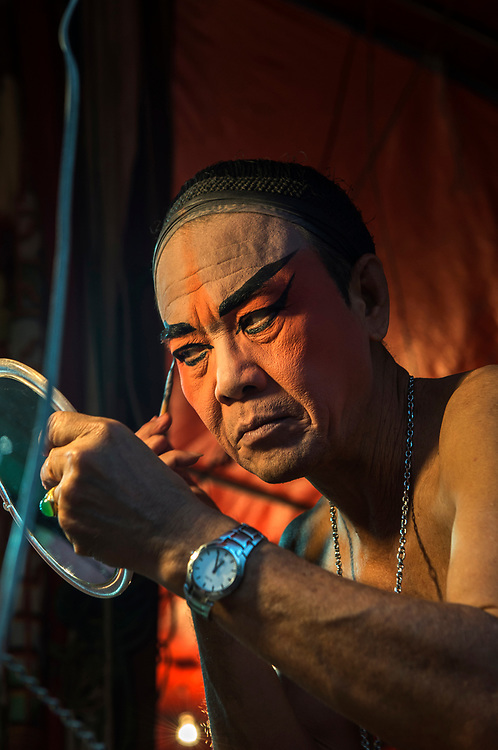 A male performer of the Sai Yong Hong chinese opera troupe preparing backstage at Wat Pai Ngoen, Thailand.