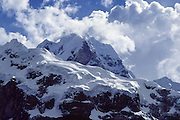"Trek to see Siula Grande (east face, 20,800 feet or 6344 meters elevation) and other spectacular peaks in the Cordillera Huayhuash, Andes Mountains, Peru, South America. Siula Grande was the subject of the gripping 2003 British docudrama ""Touching the Void."" In 1985, climbers Joe Simpson and Simon Yates scaled the treacherous Siula Grande, one of the last unconquered mountains in the Andes, but after Joe broke his leg, their descent became one of the most amazing survival stories in mountaineering history. This photo shows the northeast face, but they climbed Siula Grande from a valley on the other side (the west face) and descended along the north ridge, on the upper right. The 2003 movie is based upon Joe Simpson's harrowing book, ""Touching the Void: The True Story of One Man's Miraculous Survival."""