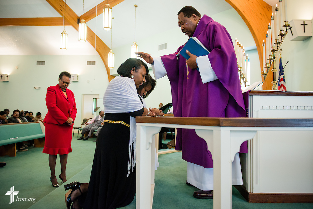 The Rev. Ulmer Marshall confirms Chelsea Pettaway (rear, kneeling) during worship at Trinity Lutheran Church on Sunday, April 6, 2014, in Mobile, Ala. Her mother Juanita Pettaway (front, kneeling) was also reinstated. LCMS Communications/Erik M. Lunsford