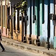 A woman walks across the street in Baracoa, Cuba on Monday July 14, 2008.