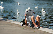 © Licensed to London News Pictures. 17/07/2014. Kingston Upon Thames, UK. A woman reads a paper on the river bank. People and animals in the sunny hot weather on the banks of the River Thames at Kingston Upon Thames today 17th July 2014. Photo credit : Stephen Simpson/LNP