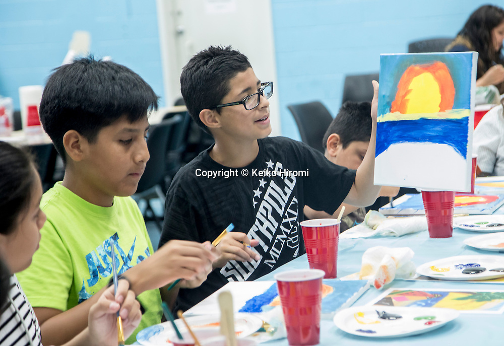 July 13, 2017: -East Boston Social Center,  East Boston, Massachusetts: Alejandro Gallego (R) showing off his paiting to his friends during painting class led by a visual artist Ayana Mack at East Boston Social Center.