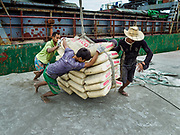 22 NOVEMBER 2017 - YANGON, MYANMAR: Workers unload bags of cement from a freighter docked on the Twante Canal in Yangon. Myanmar's road system lags behind its neighbors in Southeast Asia and a lot of cargo is still moved by ships and barges.    PHOTO BY JACK KURTZ