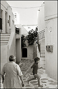 Little boy running in a street while being watched by his grandmother. Paros, Greece