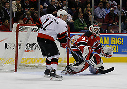 Apr 3, 2007; East Rutherford, NJ, USA; Ottawa Senators right wing Daniel Alfredsson (11) and New Jersey Devils goalie Martin Brodeur (30) battle during the second period at Continental Airlines Arena in East Rutherford, NJ.