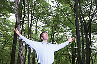 Mid adult man standing in forest with outstretched arms and closed eyes