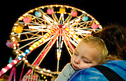 Photo by Gary Cosby Jr.  The Morgan County Fair opened Thursday night in Decatur at the Morgan County Fairgrounds.  Brayden Nicholas naps on his aunt Connie Wise's shoulder as they make the rounds.