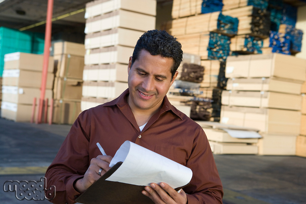 Mid-adult man with clipboard outside warehouse full of wood